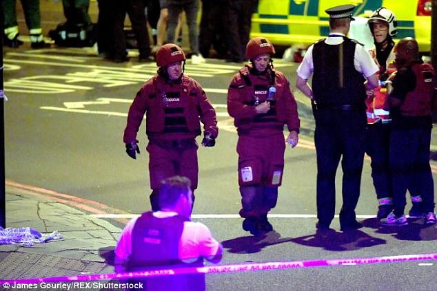 Los equipos de rescate en la escena que investigan como otros miembros del servicio de emergencia se apiñan para discutir la operación