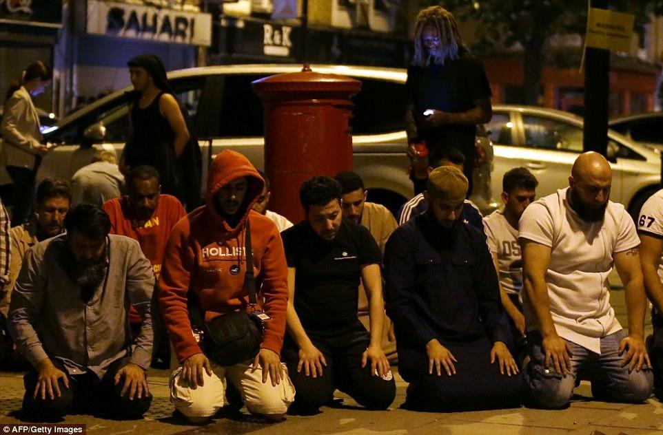 Un grupo de musulmanes orar en el pavimento después de la atrocidad.  El incidente se ha cerrado de golpe como una 'manifestación violenta de la islamofobia', con los líderes musulmanes que piden mayor seguridad en torno a las mezquitas
