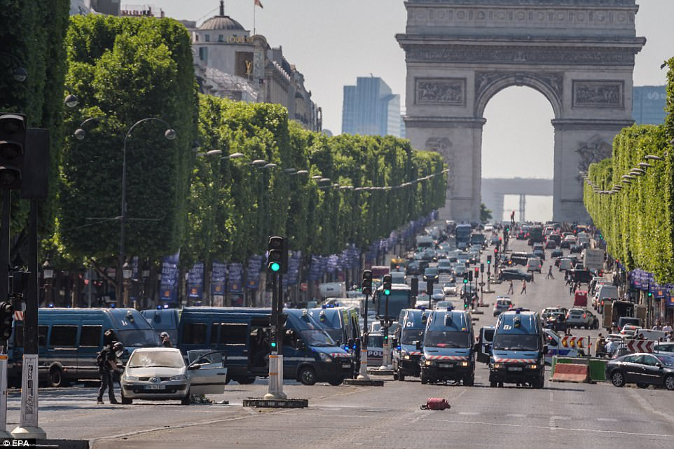 The car left abandoned on the world-famous avenue and a red canister can be seen in the middle of the road which is teeming with police officers