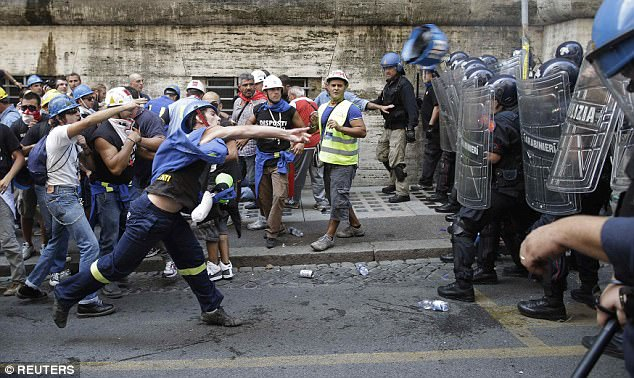 Significant splits have opened up between the European Union's so-called gilded elite and the 'simmering discontent' of ordinary citizens, a damning report has revealed. Pictured: Italian employees  battle police in Rome in 2012