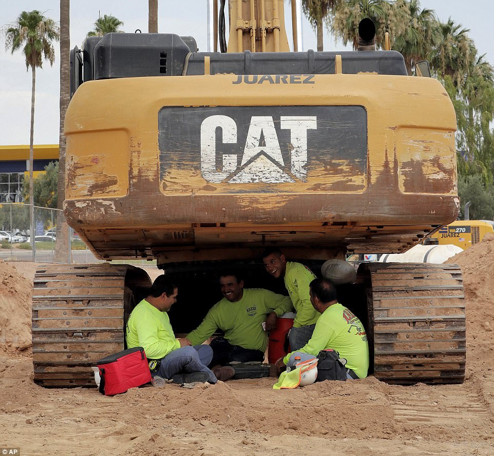 Construction works improvise and find shade underneath an excavator to avoid the head in Phoenix, Arizona