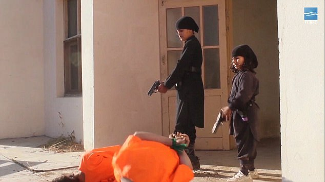 The two boys, both dressed in black, force their captives to kneel in front of them in front of the doorway of a building in Afghanistan before carrying out the executions