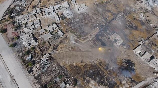 Esta imagen fija del video muestra un tanque disparando hacia su objetivo con un segundo vehículo blindado estacionado detrás de él