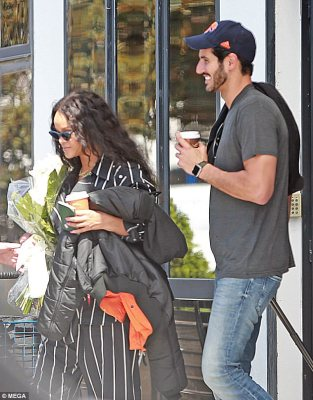 Coy: Rihanna certainly knew how to keep a huge smile on the face of her new Saudi billionaire boyfriend Hassan Jameel during their romantic holiday in Spain on Monday