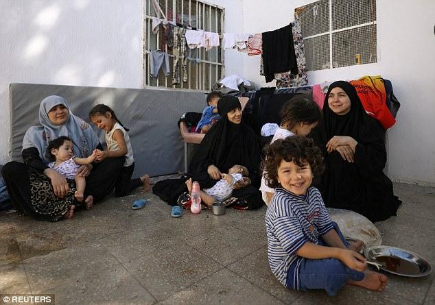 (De izquierda a derecha) tunecinos Khadouja al-Humri, Iman Othman y libanés Nour Al-Huda, esposas de los ex combatientes estado islámico, se sientan con sus hijos en un campamento para personas desplazadas en Ain Issa, al norte de Raqqa, Siria 21 de de junio de