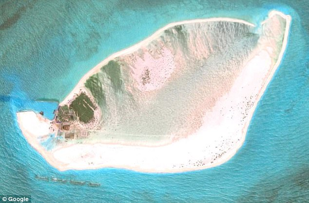 Denied: Triton Island (pictured) is claimed by China (which has built a base, far left). By sailing through the waters it claims to own, the US denied the country's ownership of the island