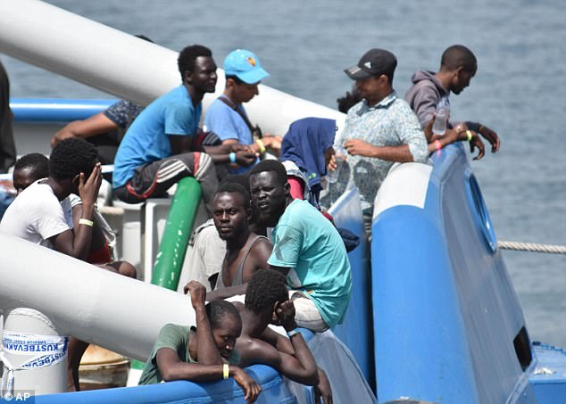 Los migrantes están en la cubierta del barco sueco Armada BKV 002, mientras esperan para desembarcar en el puerto siciliano de Catania, Italia el sábado