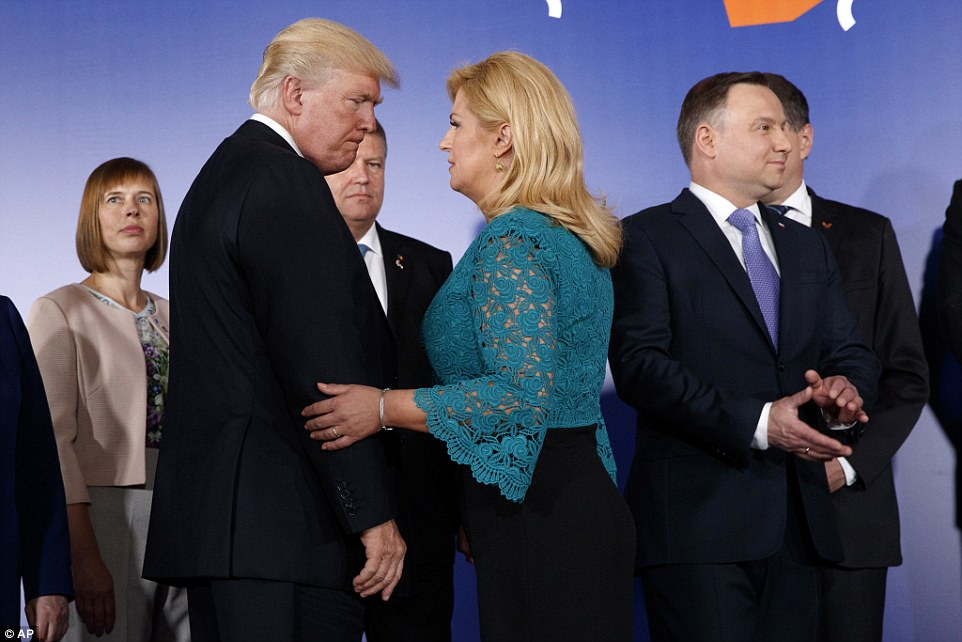 Trump talks with Croatian President Kolinda Grabar-Kitarovic, center right, as they arrive for a group photo prior to the Three Seas Initiative transatlantic roundtable in the Great Assembly Hall of the Royal Castle, in Warsaw
