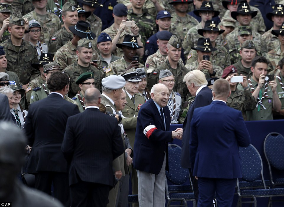 Donald Trump shake hands with veteran as dozens of others look on after delivering a speech in Krasinski Square in Warsaw, Poland on Thursday