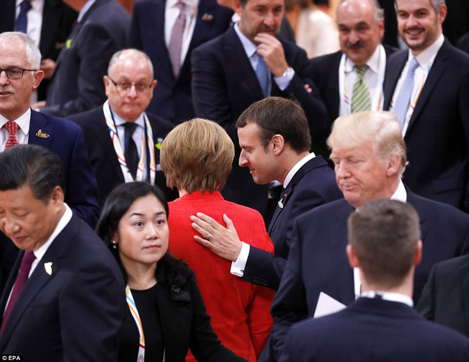 Macron (center right) talks to Merkel (center left, back to camera) as Trump (right) looks on during the opening session of the G20