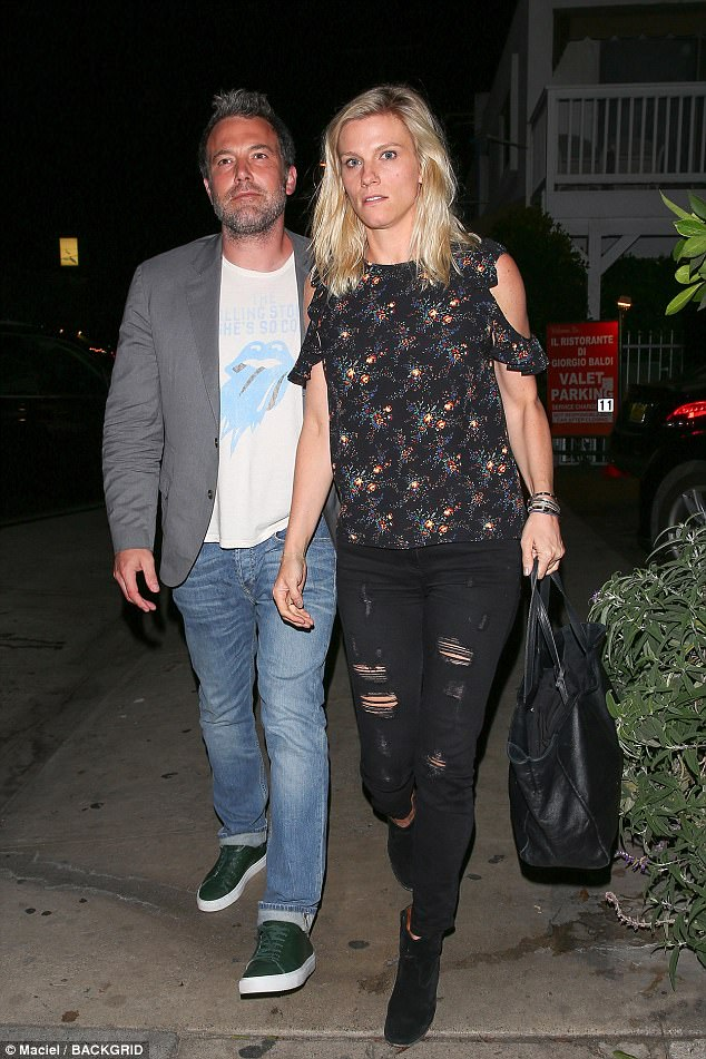 Staying close: The movie star paired his denim bottoms with a Rolling Stones top and a grey blazer