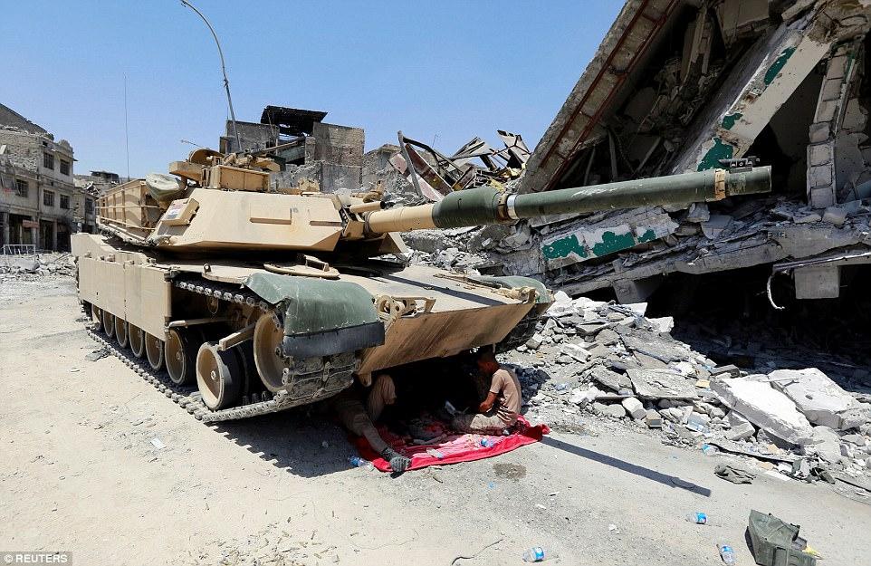 Dos soldados se imaginan refugiándose bajo un tanque en el abrasador calor iraquí durante las operaciones para volver a tomar Mosul