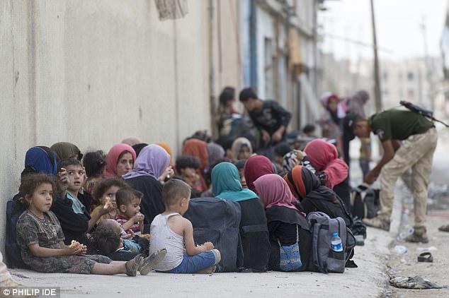 En la foto: Los niños en el casco antiguo de Mosul comen comida mientras los trabajadores humanitarios y los soldados liberadores los protegen