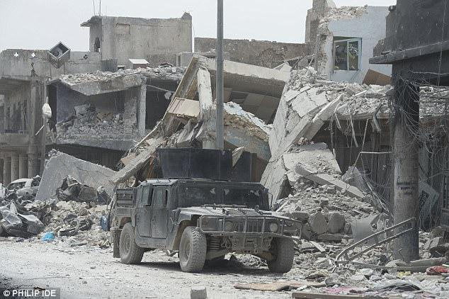 Un Humvee conduce a través de los escombros de Mosul central mientras que los soldados luchan para librarlo de los 100 o más fanáticos islámicos del estado todavía allí.  Mosul, una vez hogar de dos millones de personas, incluyendo muchos cristianos, kurdos y yazidis, fue capturado inesperadamente fácilmente por unos cientos de jihadis en 2014