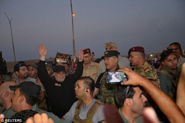 El primer ministro iraquí Haider al-Abadi es retratado con los brazos en alto mientras está rodeado de personal militar en Mosul, Irak