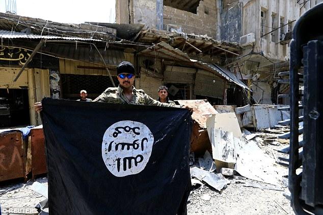 El ISIS solía ser parte de Al Qaeda antes de separarse del grupo en 2014 cuando las fuerzas occidentales se retiraron de Irak, antes de establecer su llamado califato (foto, un soldado iraquí tiene una bandera ISIS capturada)