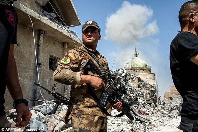 El humo se levanta sobre la ciudad vieja de Mosul mientras que los miembros de las fuerzas de seguridad guardan la guardia