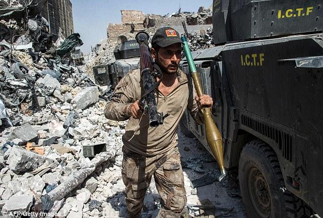 El militar iraquí lleva una granada propulsada por cohetes a través de camiones blindados mientras los servicios de seguridad patrullan la ciudad vieja de Mosul