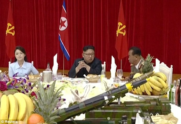 She sat next to the 33-year-old tyrant on a table laden with bowls of fruit, bottles of booze and - bizarrely - miniature replica missile launchers