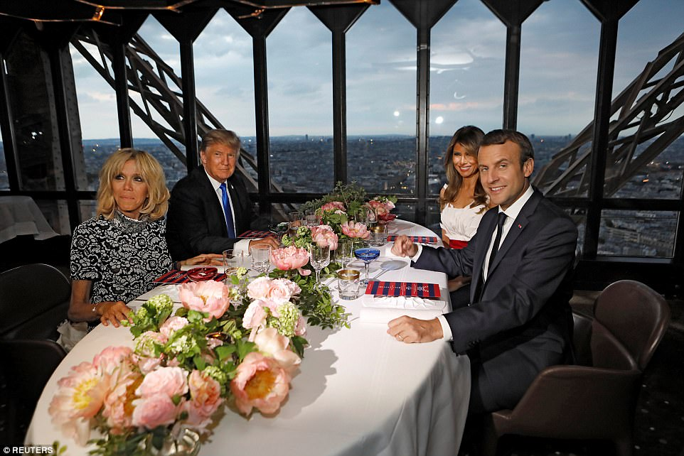 Donald Trump seated himself next to Brigitte Macron, who he'd shared an uncomfortable handshake with earlier in the day that lingered on a little too long