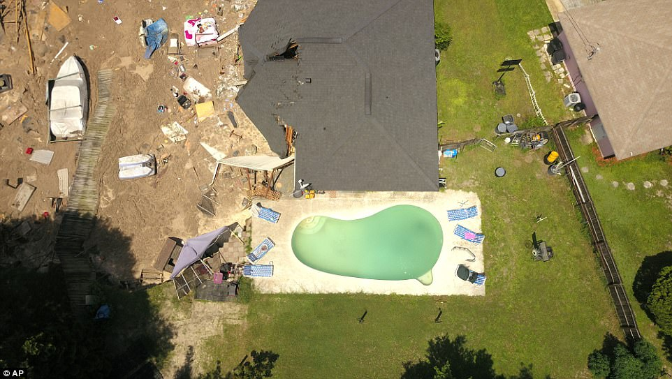 A swimming pool on the edge of the sinkhole is left intact, but authorities fear more structures would be damaged