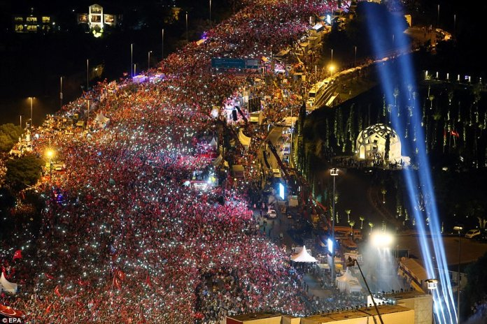 Thousands of people (pictured in an aerial photo above) filled the streets wearing red and carrying Turkish flags to mark the year anniversary of the failed coup