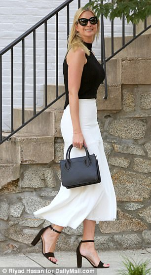 Looking sharp: The 35-year-old was wearing a chic monochrome outfit, opting for a floaty white skirt and sleeveless black top