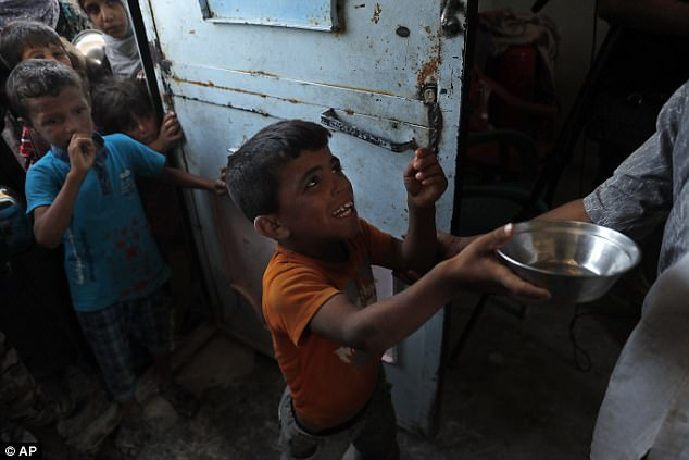 A Syrian displaced boy holds a pot as he bagging a man to give him food at the entrance of the main kitchen of a refugee camp, in Ain Issa town