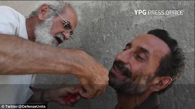 Un residente sirio sonríe mientras el barbero corta la barba que se vio obligado a crecer por ISIS