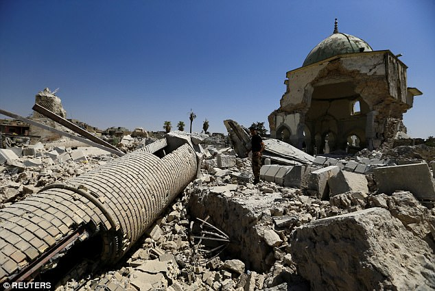 A member of the Iraqi Counter Terrorism Service (CTS) stands next to the ruined Grand al-Nuri Mosque in the Old City of Mosul