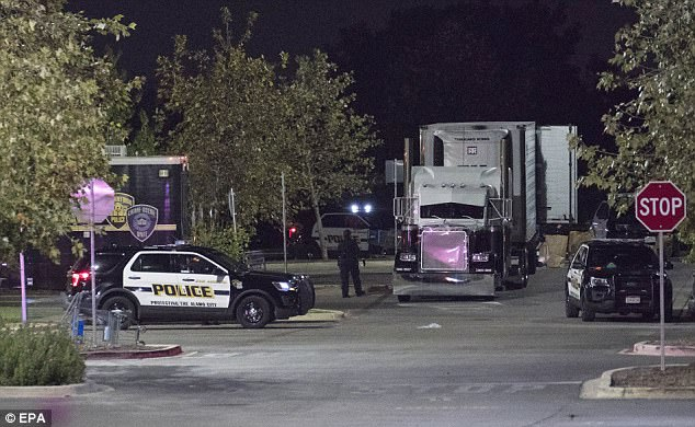 Eight people, including two children, were founded dead. Police are investigating the incident as a 'human trafficking' case (Pictured, police officers near a white truck in the parking lot)