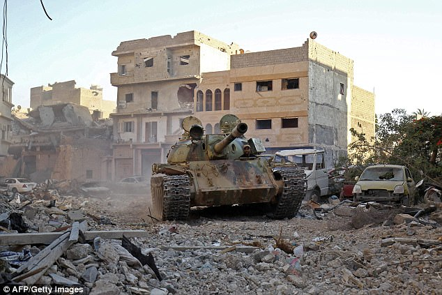 A member of the self-styled Libyan National Army, loyal to the country's east strongman Khalifa Haftar, rides in a tank as it drives down a street through the rubble in Benghazi's central Akhribish district on July 19, 2017 following clashes with militants