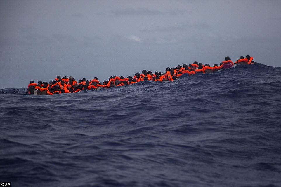 Docenas de inmigrantes que llevan flotadores de flotadores de color naranja brillante flotan en el mar a unos 15 kilómetros de la costa de Sabratha, Libia