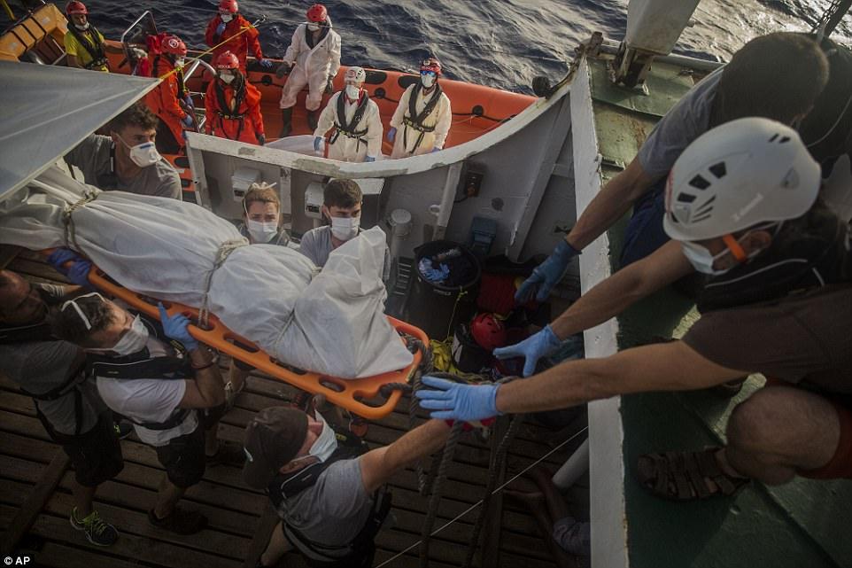 Los trabajadores humanitarios de Proactiva Open Arms recuperan cadáveres de inmigrantes subsaharianos dentro de un barco de goma en el Mar Mediterráneo.  Más de 120 inmigrantes fueron rescatados el martes del mar Mediterráneo, mientras que 13 más - incluyendo mujeres embarazadas y niños - murieron en una balsa de goma, según un grupo de rescate español