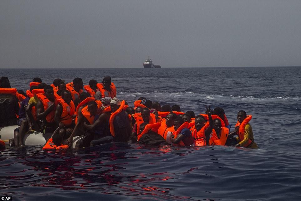Un migrante sostiene dos dedos a la cámara mientras docenas de otros esperan a que el bote al que viajan se hunda bajo la superficie del agua