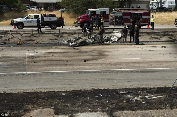 Authorities said the plane came down on a highway, killing the four people aboard, while also snarling traffic and leaving behind blackened wreckage (pictured)