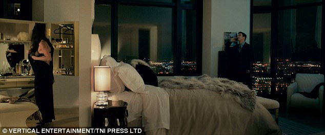 Oblivious: With an illuminated city-scape visible through a large, floor-to-ceiling window, husband Mark - played by Dean McDermott appears completely indifferent to his wife's semi-naked state while distractedly talking on his cell-phone