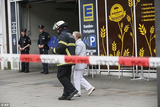 La policía armada ha sido representada en la escena habiendo acordonado el área.  Un bombero fue fotografiado acompañando a una anciana de la escena