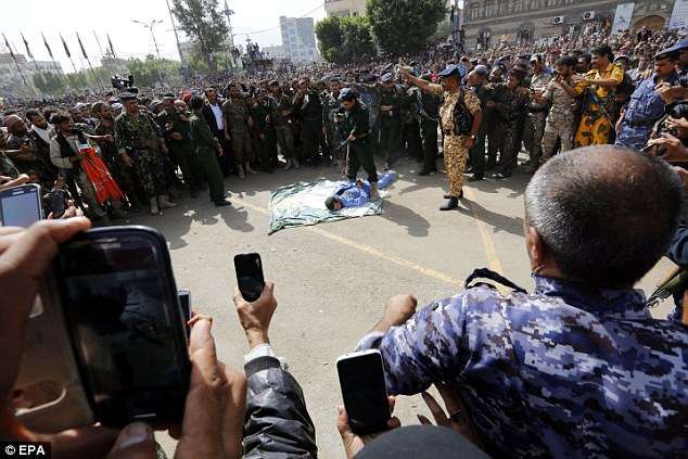 Onlookers filmed the execution on their phones while a television crew gathered around to get the best angle (rear left)
