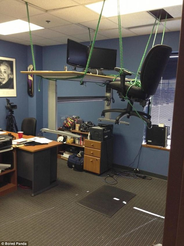 This office worker is going to have a hard time meeting deadlines with his desk suspended from the ceiling