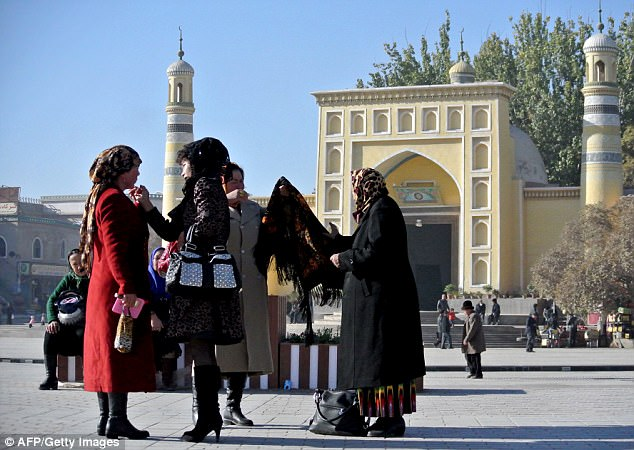 Uyghur women outside a mosque in Hotan, China's Xinjiang province (File photo)