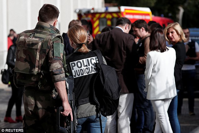 Attack: Police and military work near the scene where French soldiers were hit in what the local mayor has branded a 'deliberate, odious act of aggression'