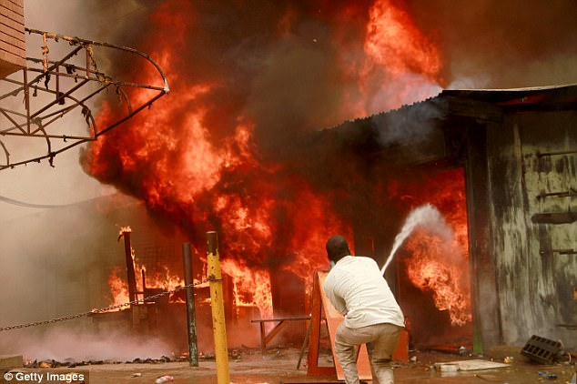 A local man tries to extinguish fire caused by supporters of the opposition candidate Raila Odinga