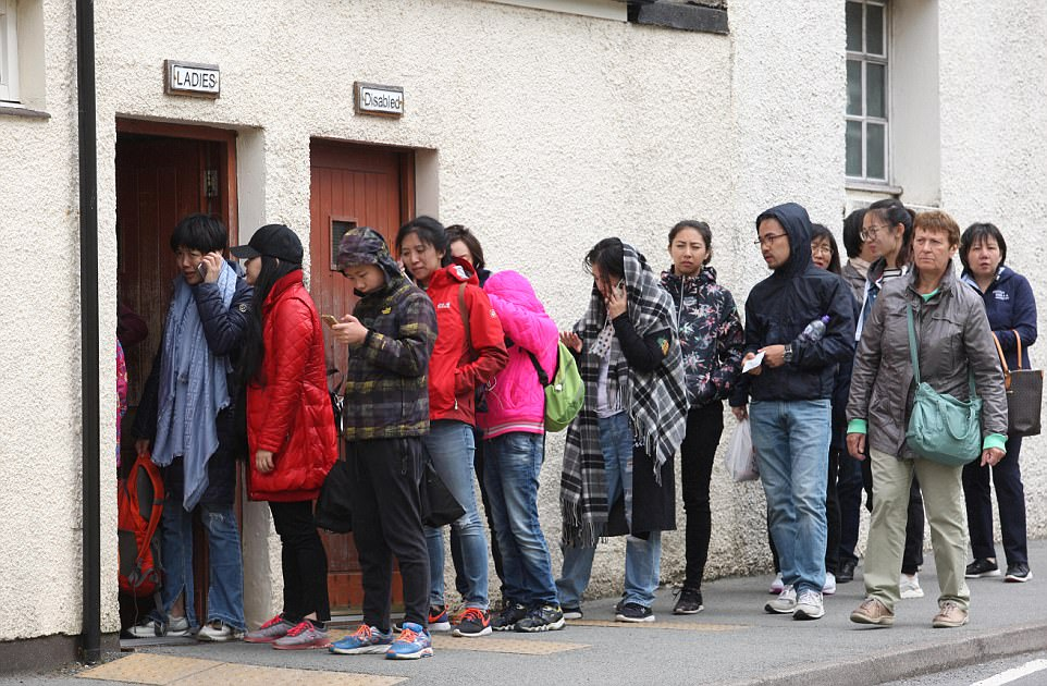 The island has become increasingly popular with holidaying Britons and foreign tourists alike. Here people an be seen in a queue for the public toilets in Portree on the Isle of Skye