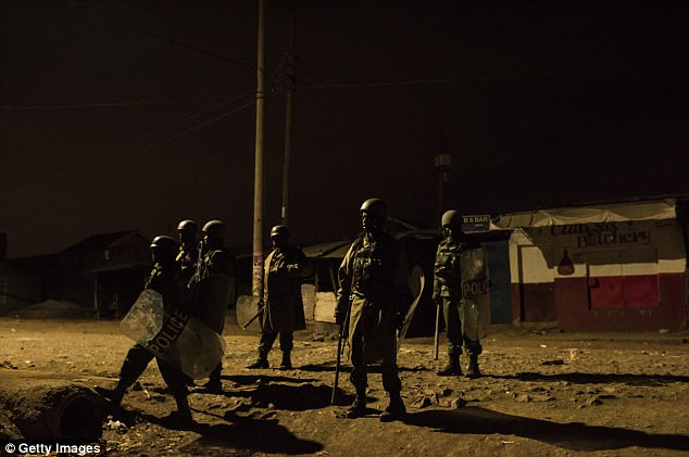 Kenyan police officers clear a street in the Kawangware slum after an officer was hit in the head with a rock