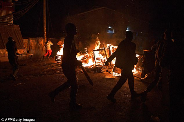 Protestors loot and burn premises belonging to the Kikuyu tribe on August 11 in the Kibera slum of Nairobi