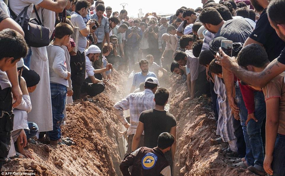 Miembros de los Cascos Blancos Sirios entierran a sus compañeros voluntarios que fueron muertos a tiros temprano esta mañana en una emotiva ceremonia en Sarmin, una ciudad controlada por yihadistas a seis millas de la ciudad noroccidental de Siria, Idlib