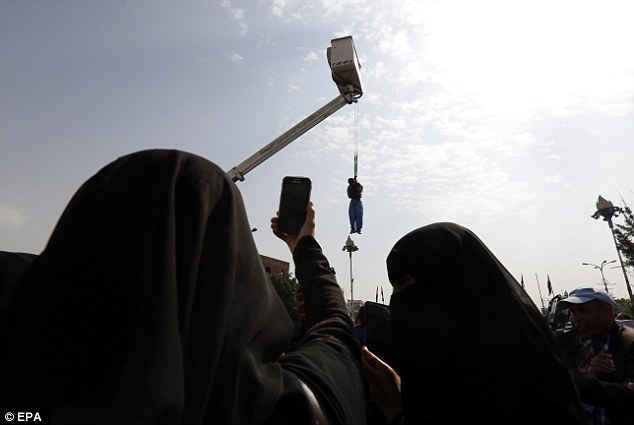 Spectacle: A woman takes a photo of the body of al-Saket as it is strung up on a crane
