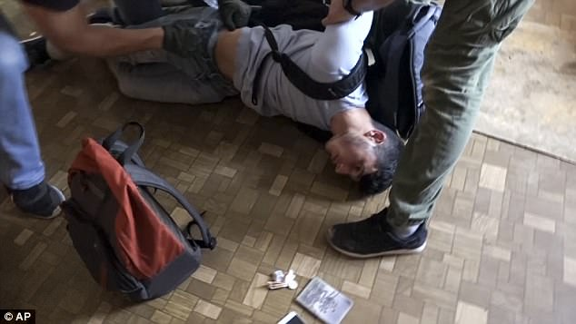 Taken down: Russian intelligence officers arrest a man on suspicion of plotting a series of terrorist attacks outside Moscow