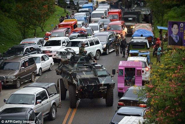 Un vehículo blindado de transporte de personal se mueve entre vehículos atascados de residentes que huyen de Marawi
